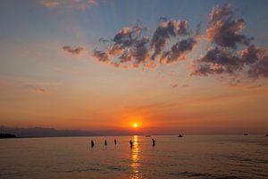 Vissers trekken een net het strand op, om vissen te vangen op het strand bij zonsondergang, Kuta, Ba