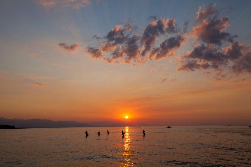 Vissers trekken een net het strand op, om vissen te vangen op het strand bij zonsondergang, Kuta, Ba van Tjeerd Kruse