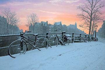 Zonsondergang in besneeuwd Amsterdam in de winter in Nederland von Nisangha Masselink