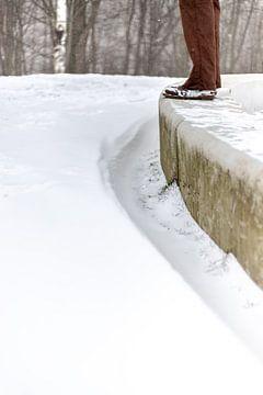 Een man staand op een cementenbalk met sneeuw