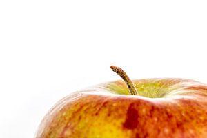 Een close-up van een appel met steeltje tegen een witte achtergrond