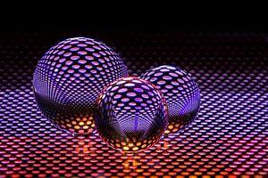 3 kristallen bollen met paarse kleur weerkaatst van