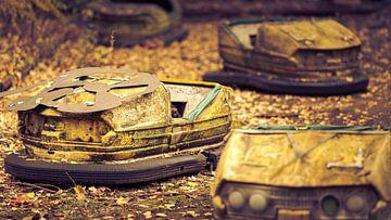 Roestige botsauto's in het pretpark van de spookstad Prypyat bij Tsjernobyl van Robert Ruidl