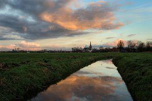 De stad IJlst in Friesland met op de voorgrond een spiegeling van de lucht in een sloot. One2expose