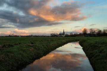 De stad IJlst in Friesland met op de voorgrond een spiegeling van de lucht in een sloot. One2expose  van Wout Kok