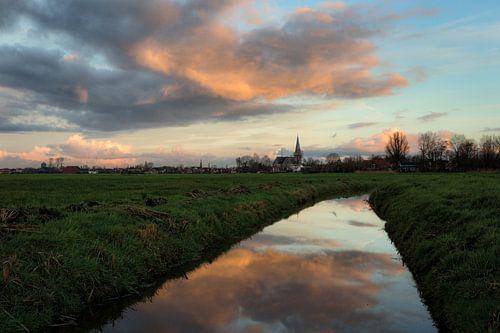 De stad IJlst in Friesland met op de voorgrond een spiegeling van de lucht in een sloot. One2expose  van