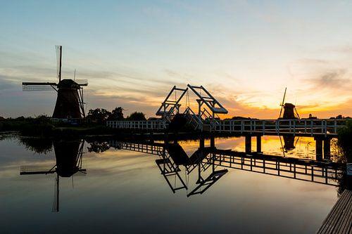 Brug met molens bij zonsondergang in Kinderdijk