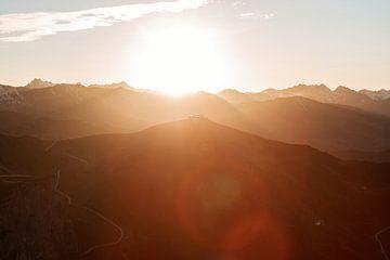 Warme lichtstralen over bergtoppen in de oostenrijkse alpen. Lens flares van Hidde Hageman