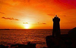 Men Ruz vuurtoren aan roze granietkust bij zonsondergang van