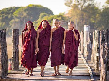 Boeddhistische monniken op een brug nabij Mandalay, Myanmar van Teun Janssen