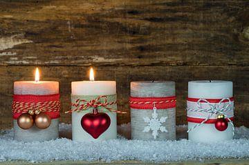 Feestelijke adventkaarsen voor de kersttijd met versiering op sneeuw van Alex Winter