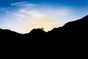 Silhouette van man die berg beklimt bij ondergaande zon. Wout Kok One2expose van Wout Kok