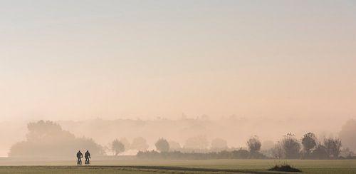 Radfahrer in den Wiesen im Morgennebel von Daan Kloeg