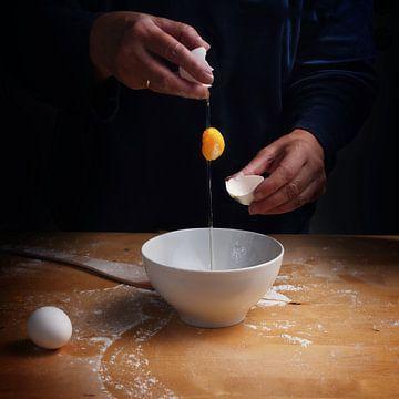 oudere vrouwenhanden breken een ei met vallende eierdooier over een kom, houten keukenplank, donkere van Maren Winter