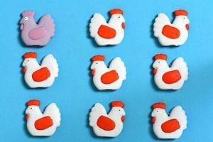 Verschiedene Figuren von Hühnern vor blauem Hintergrund