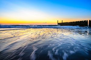 In de golven rond zonsondergang op het strand van Domburg van