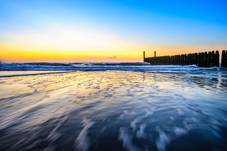 In de golven rond zonsondergang op het strand van Domburg