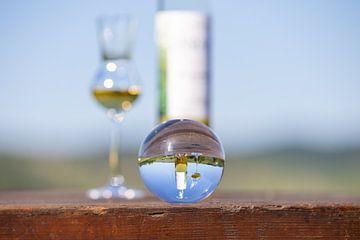 Glaskugel mit Mosellandschaft, Tresterflasche und Glas auf Holztisch von Reiner Conrad