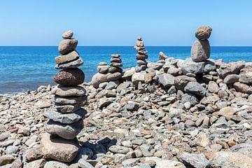 Gestapelde stenen op strand van Madeira Portugal van Ben Schonewille