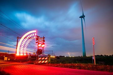 Ein Gewitter, das sich an einem Windmühlen- und Bahnübergang nähert. von Stefan Verkerk