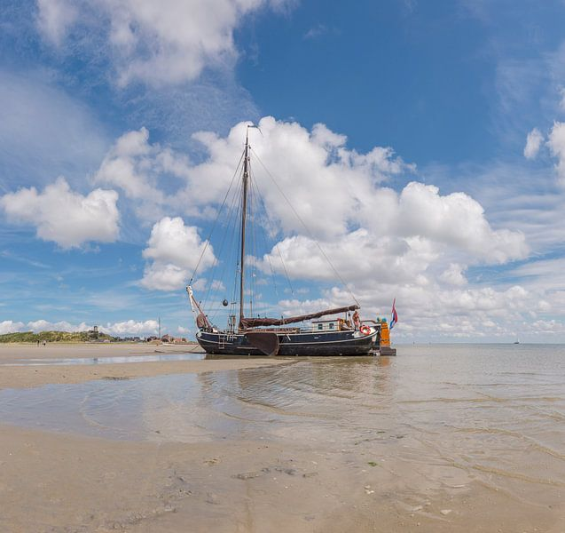 Een platbodem zeilboot op een drooggevallen wad, West-Terschelling, Wadden eiland, Friesland van Rene van der Meer