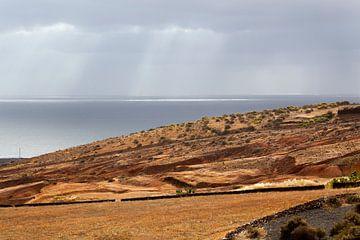 Zonnestralen op het water en landschap bij Arrieta op Lanzarote van Peter de Kievith Fotografie