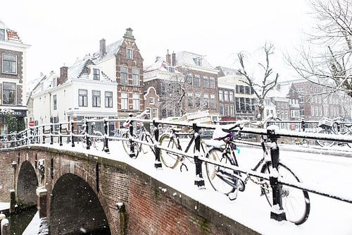 Winter in Utrecht. Fietsen op de Oudegracht onder een sneeuwlaag. van