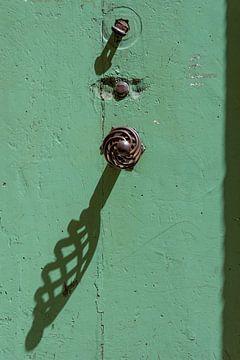 Smeedijzeren ornamenten op een groene rustieke deur van Wil Wijnen