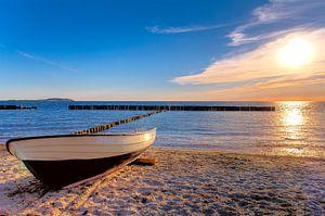 Solnedgång, strand, hav och båt på stranden i Rügen.