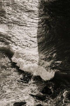 Zwart wit beeld van woeste golven in de namiddagzon van Moniek Kuipers
