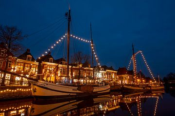 Geschmückte Boote im Hafen von Dokkum in den Niederlanden in der Nacht zur Weihnachtszeit von Nisangha Masselink