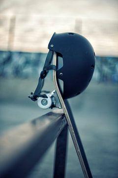 Skateboard met zwarte helm tegen een rail in skatepark van