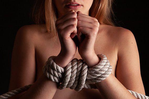 Naakte vrouw met haar handen vastgebonden voor haar lichaam. van Retinas Fotografie