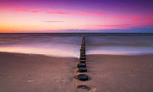 Kribben aan zee bij zonsondergang