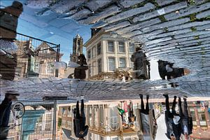 Tussen de regenbuien door weerspiegelt de Utrechtse Domtoren in een plas.