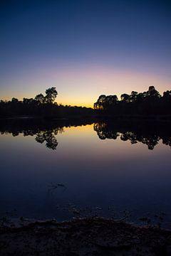 Zonsondergang met prachtige weerspiegeling in een windstil water.