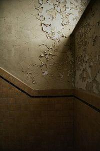 Een oude muur met bladderend behang