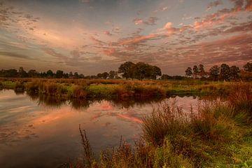 Kleurrijke wolken reflecterend in het water van Tom Kruissink