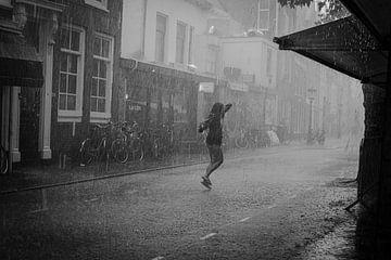 Junge Frau tanzt im Regen in schwarz und weiß von Bart van Lier