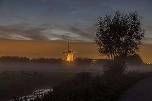 Verlichte molen Kinderdijk in mistbank
