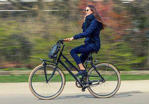 Een jonge vrouw fietst door het park in Amsterdam.  van