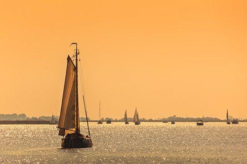 Friese zeilschepen bij zonsondergang van