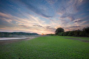 Coucher de soleil sur l'Elbe en Allemagne, avec une tache de nuages et de jeunes herbes au premier p sur Joost Adriaanse