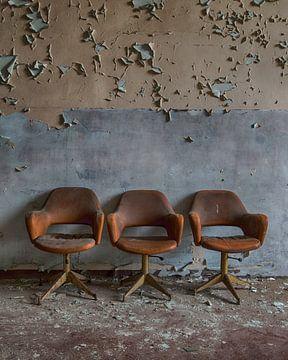 3 stoelen voor de muur van