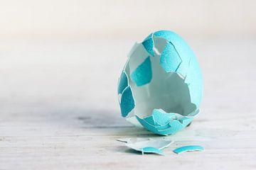 œuf de Pâques vide cassé en turquoise sur un fond de bois peint en blanc, concept pour les tradition sur Maren Winter