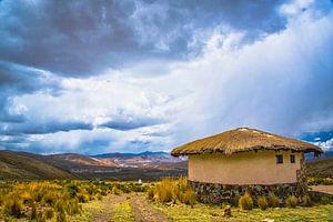 Dreigende lucht boven traditionele ronde hut op de hoogvlakte van het Andesgebergte, Peru van Rietje Bulthuis