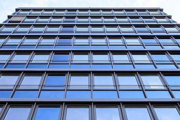 Spiegelde Häuserfassade moderner Bürogebäude bei blauem Himmel von MPfoto71