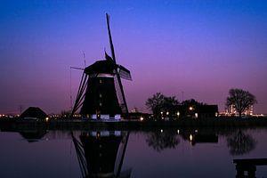 Hollandse windmolen bij een rivier tijdens het blauwe uur van