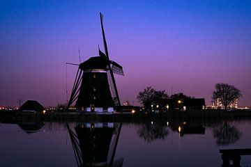 Niederländische Windmühle in der Nähe eines Flusses während der blauen Stunde von Menno van der Haven