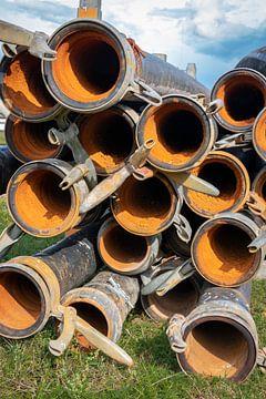 Tubes en plastique empilés dans l'herbe utilisés pour le drainage des puits sur Henk Hulshof